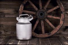 Aluminium water can and old wheel Royalty Free Stock Photo
