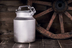 Aluminium water can and old wheel Stock Photography