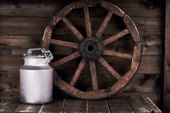 Aluminium water can and old wheel Royalty Free Stock Image