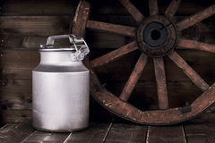 Aluminium water can and old wheel Stock Photos