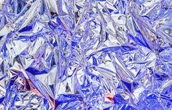 Aluminiumfolie met multi-colored verlichting Achtergrond en textuur van aluminiumfolie stock afbeeldingen