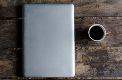 Aluminiumnotitieboekje (laptop) met kop van hete koffie op houten lijst Stock Foto's