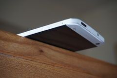 Aluminiumtelefon, das am Rand des Holztischs als Konzept der Stabilität balanciert Stockbild