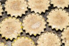 Aluminiumvormen voor baksel cupcakes gevuld deeg en bestrooid met suiker Stock Afbeeldingen