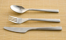 Aluminiumware. Knife, fork and spoon on a woben bamboo support Stock Photos