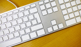 Aluminum blank keyboard on wooden desk Royalty Free Stock Images