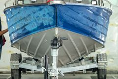 Aluminum boat painting procedure at service center. Repairing boat body by puttying close up work after the accident by working sanding primer before painting stock photography