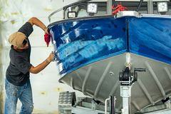 Aluminum boat painting procedure at service center. Repairing boat body by puttying close up work after the accident by working sanding primer before painting royalty free stock photography