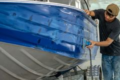 Aluminum boat painting procedure at service center. Repairing boat body by puttying close up work after the accident by working sanding primer before painting stock photos