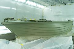 Aluminum boat painting procedure at service center. Repairing boat body by puttying close up work after the accident by working sanding primer before painting royalty free stock photos