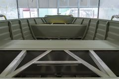 Aluminum boat painting procedure at service center. Repairing boat body by puttying close up work after the accident by working sanding primer before painting stock image
