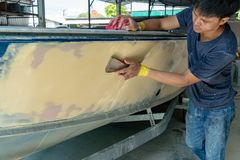 Aluminum boat painting procedure at service center. Repairing boat body by puttying close up work after the accident by working sanding primer before painting stock photo