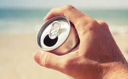 Aluminum can of beer in male hand, retro toned. Aluminum can of beer in male hand with blurred beach and sea on a background, vintage toned photo, retro tonal Stock Photos