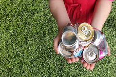 Aluminum Cans Crushed For Recycling. In a Childs Hands Stock Photos