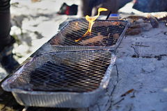 Aluminum disposable throwaway outdoor grill used in winter as a temperature contrast between hot grill grid and freezing snow du. Ring the December cookout Royalty Free Stock Photos