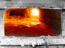 Aluminum dross layer. Looking inside an aluminum melting furnace, in a foundry, with liquid metal and the oxidize dross layer on it royalty free stock photo
