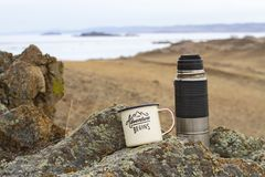 Aluminum enameled camp mug with tea and a metal thermos on the stony shore of Lake Baikal in early spring. Aluminum enameled camp mug with tea and a metal Stock Images