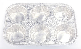 Aluminum foil baking tray for 6 cupcakes on white background. Aluminum foil baking tray for 6 cupcakes on white background, homemade baking concept Stock Photo