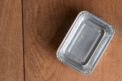 Aluminum foil tray on table. Aluminum foil tray on wood table background stock photo