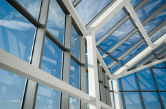 Aluminum and glass construction. Modern office building glass ceiling against blue skies Stock Images