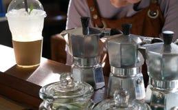aluminum krukakaffebryggare på stångräknare & barista i kafé stov Arkivfoto