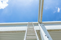 Aluminum ladder pointing towards on next level, concrete edifice. Architecture concept, concrete structure girders, ladder to the sky reaching for the higher Royalty Free Stock Image