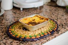 Aluminum magasin med lagade mat lasagner p? tabellen royaltyfri foto