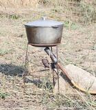 The sooty cauldron on a tripod on the river Bank. Aluminum pot for cooking in the journey Stock Image