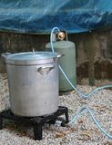 Aluminum pot with gas canister in the camp kitchen while prepari. Big aluminum pot with gas canister in the camp kitchen while preparing the meal Stock Photo