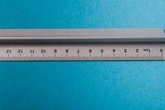 Aluminum ruler on blue background Royalty Free Stock Image