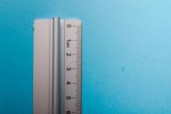 Aluminum ruler on blue background Stock Photography