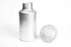 Aluminum saltshaker with the top off. Metal salt shaker standing with its lid lying next to it royalty free stock photo