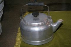 Aluminum tea kettle or coffee pot with lid 1940s to 1960s. Kettle sitting on a green cloth or place mat. The kettle has a black wooden handle royalty free stock photography