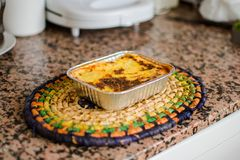 Aluminum tray with cooked lasagna on table royalty free stock photo