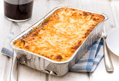 Aluminum tray with cooked lasagna on table royalty free stock photos