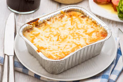 Aluminum tray with cooked lasagna on table Stock Images