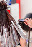 Alumminium foil helps to dye. Woman making her hair lighter.  Royalty Free Stock Image