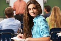 Alumno adolescente femenino en sala de clase Foto de archivo