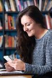 Alumno adolescente femenino que manda un SMS en sala de clase foto de archivo