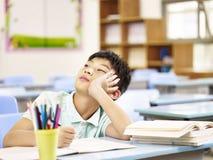 Alumno asiático que piensa en sala de clase Fotografía de archivo libre de regalías