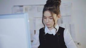 Alumno bastante femenino que trabaja entusiasta con PC 4K almacen de metraje de vídeo