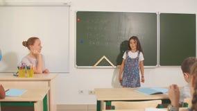 Alumno con el profesor en sala de clase Muchacha cerca de la demostración de la pizarra su preparación almacen de metraje de vídeo