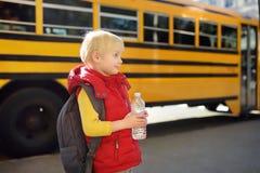 Alumno con la cartera y la botella de agua con el autob?s escolar amarillo en fondo imagen de archivo