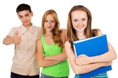 Alumno con una carpeta azul con sus amigos Fotos de archivo libres de regalías
