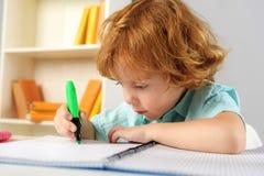 Alumno concentrado que se sienta con el marcador Fotografía de archivo libre de regalías
