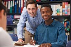 Alumno de Helping Male Teenage del profesor en clase Imagen de archivo