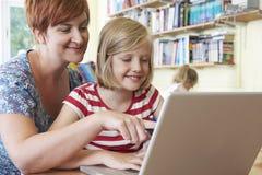 Alumno de la escuela con el profesor Using Laptop Computer en sala de clase Fotos de archivo libres de regalías