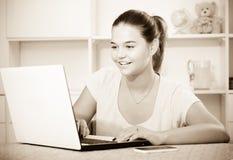 Alumno de la escuela de la muchacha que mecanografía en el ordenador portátil mientras que estudia dentro Foto de archivo libre de regalías