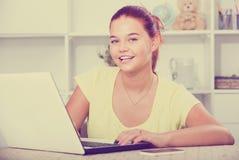 Alumno de la escuela de la muchacha que mecanografía en el ordenador portátil mientras que estudia dentro Imagen de archivo libre de regalías