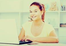Alumno de la escuela de la muchacha que mecanografía en el ordenador portátil mientras que estudia dentro Fotografía de archivo